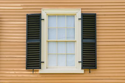 Exterior view of a double-hung window with black shutters
