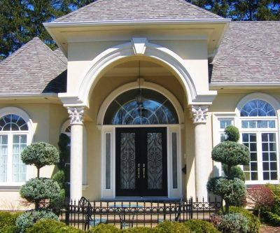 Large, modern home featuring double entry doors with intricate glass patterns