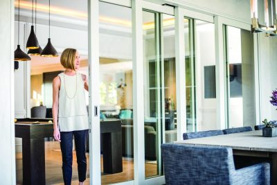 Woman looking out at her back patio through sliding glass patio doors
